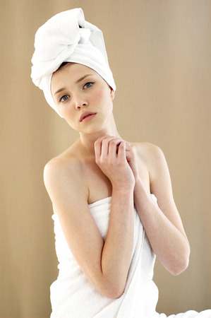 A woman with her hair and body wrapped up in towel looking at the camera photo