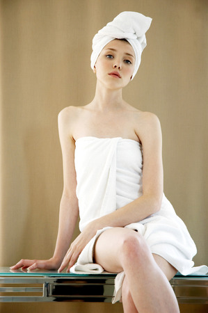 hair wrapped up: A woman with her hair and body wrapped up in towel sitting on the table