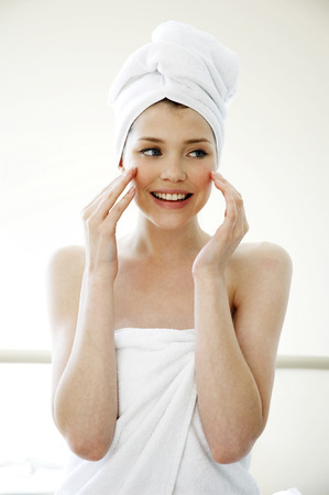 undereye: A woman with her hair and body wrapped up in towel smiling while applying under eye cream