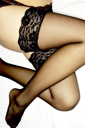 undergarment: A pair of legs in black sexy lacy undergarment and stockings