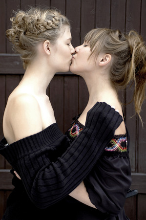 beautiful lesbian: Side shot of a woman kissing her partner