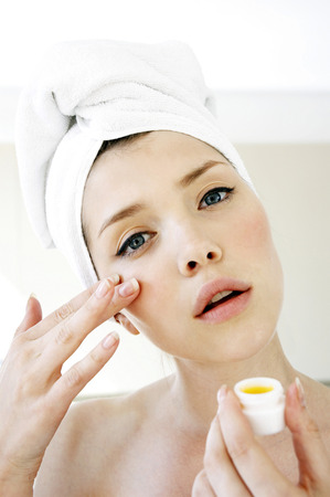 A woman with her hair and body wrapped up in towel applying under eye cream photo