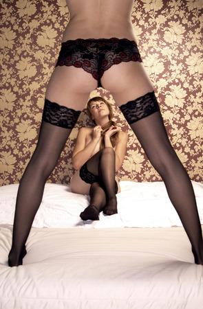 lesbians: Dos mujeres en ropa interior de encaje sexy negro y medias con una sentada y otra de pie en la cama Foto de archivo