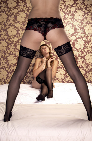 Two women in black sexy lacy undergarment and stockings with one sitting and the other one standing on the bed photo