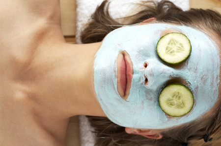 Top angle view of a woman doing facial mask with sliced cucumbers covering her eyes photo