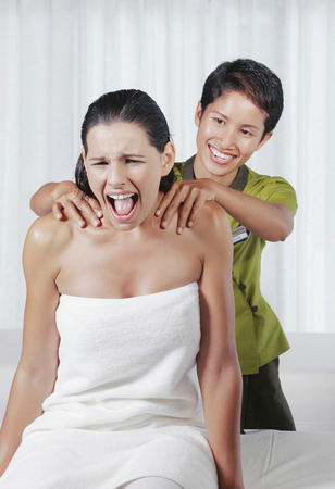 A lady screaming in pain while the Siamese massage therapist massaging her photo