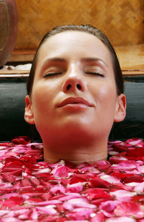 spoiling: A woman relaxing in a bathtub full of flower petals with her eyes closed