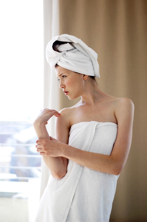 hair wrapped up: A woman with her hair and body wrapped up in towel standing near the window