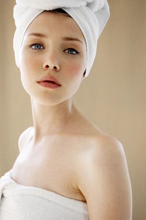 hair wrapped up: A woman with her hair and body wrapped up in towel looking at the camera Stock Photo