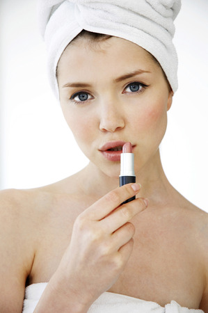 hair wrapped up: A woman with her hair and body wrapped up in towel applying lipstick