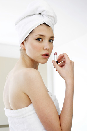 hair wrapped up: Side shot of a woman with her hair and body wrapped up in towel holding a lipstick Stock Photo