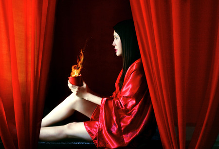 red bathrobe: Side shot of a woman in red bathrobe sitting down holding burning cup of coffee Stock Photo
