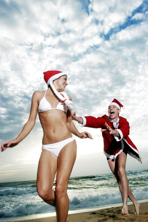 A guy in Santa suit chasing after a lady in bikini and a Santa hat photo