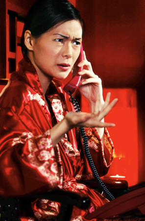 oriental bathrobe: An angry looking woman in oriental bathrobe talking on the phone