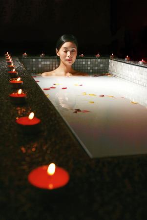 花びら: その周りに香りキャンドルと花びらのバスタブで入浴女性
