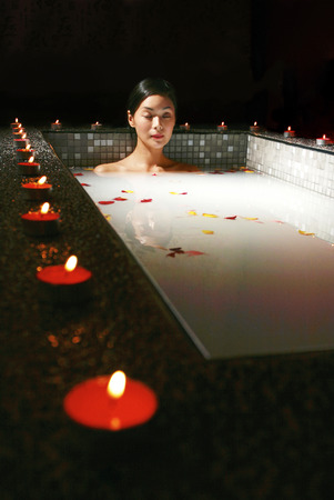 spoiling: A lady bathing in a bathtub of flower petals with lit scented candles around it