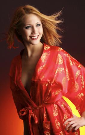 red bathrobe: A studio shot of a lady in red bathrobe smiling