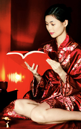 oriental bathrobe: A woman in oriental bathrobe reading a book