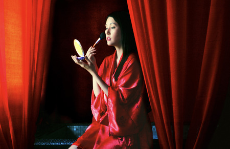 red bathrobe: A woman in red bathrobe putting on brushing some blusher on her cheek
