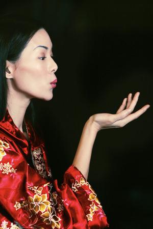 oriental bathrobe: Side shot of a lady in oriental bathrobe blowing a kiss