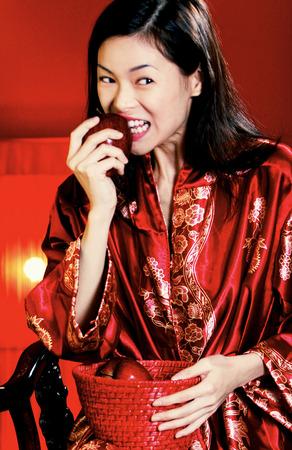 oriental bathrobe: A woman in oriental bathrobe biting a red apple