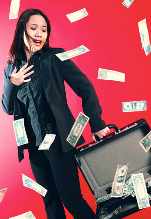 A lady carrying an opened briefcase with all the money flying out from it photo