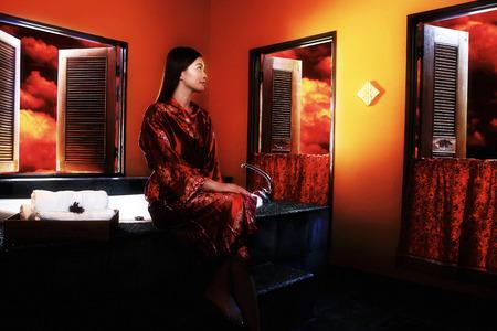 red bathrobe: A lady in oriental bathrobe sitting in a bathroom