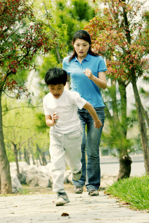 A woman chasing after a young boy  photo