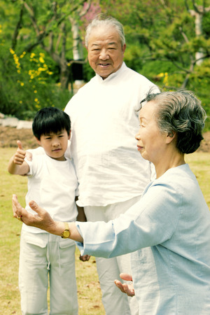 A boy watching his grandmother practising tai chi  photo