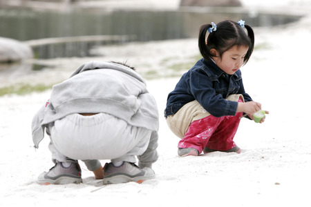 squatting down: A boy and a girl squatting down playing with sand  Stock Photo