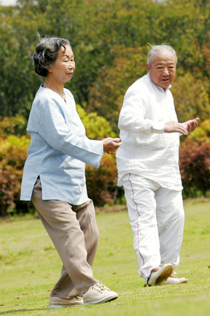 An old man and woman practising tai chi