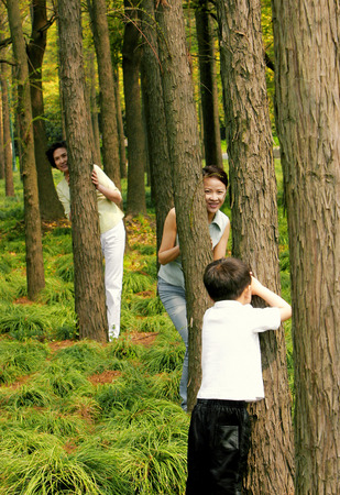 A boy playing hide and seek with his mother and grandmother