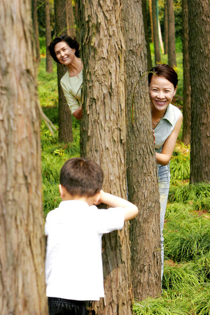 A boy playing hide and seek with his mother and grandmother  photo