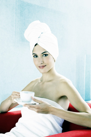 Woman in towel drinking a cup of coffee