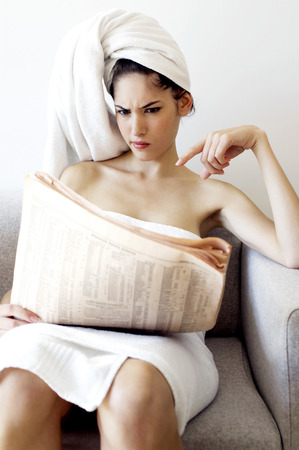 Woman in towel reading newspaper  photo