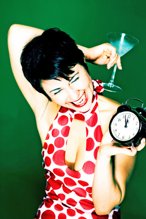 Woman in red and white polka dots dress holding a glass of cocktail and an alarm clock  photo
