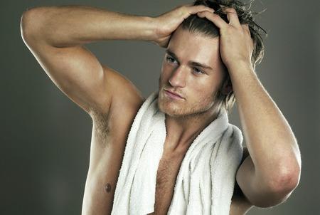 Shirtless man applying gel on his hair