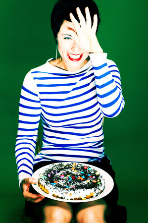 Woman in blue and white stripes blouse holding a cake  Reklamní fotografie