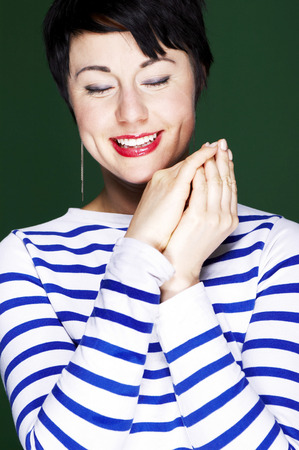 Woman in blue and white stripes blouse closing her eyes  Reklamní fotografie