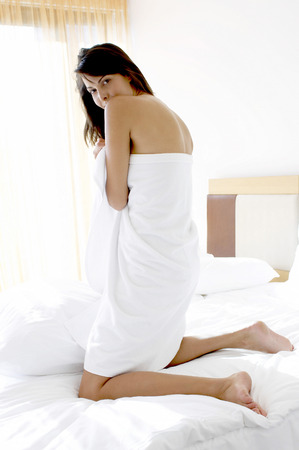 Back shot of a woman covering her body with a towel  photo