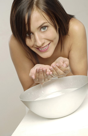 Woman flashing a smile at the camera while washing her face  photo