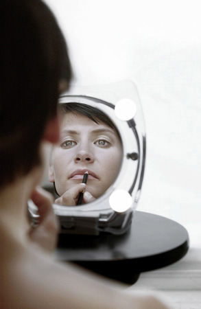 captivation: Mirror reflection of a woman applying lip liner