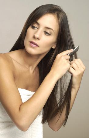 untangle: Woman in towel combing her hair  Stock Photo