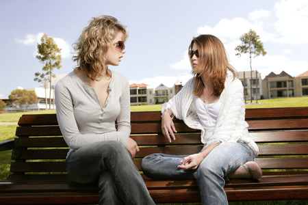 chit: Two teenage Caucasian girls chit chatting in campus area Stock Photo