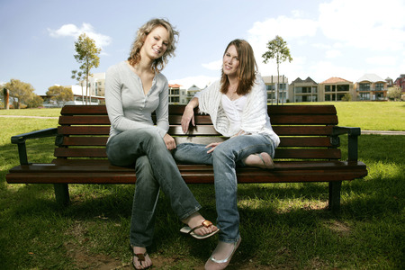 Two teenage Caucasian girls relaxing and chit chatting on a bench photo