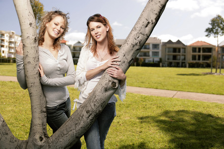 Teenage girls holding the tree branches looking at the camera photo