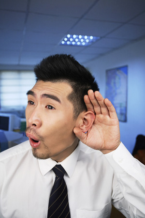 Businessman with cupped hand on ear photo