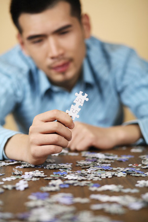 Businessman looking at the pieces of jigsaw puzzle photo