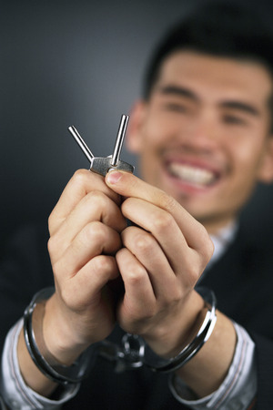 Handcuffed businessman with keys photo