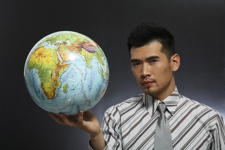 Businessman holding up a globe photo
